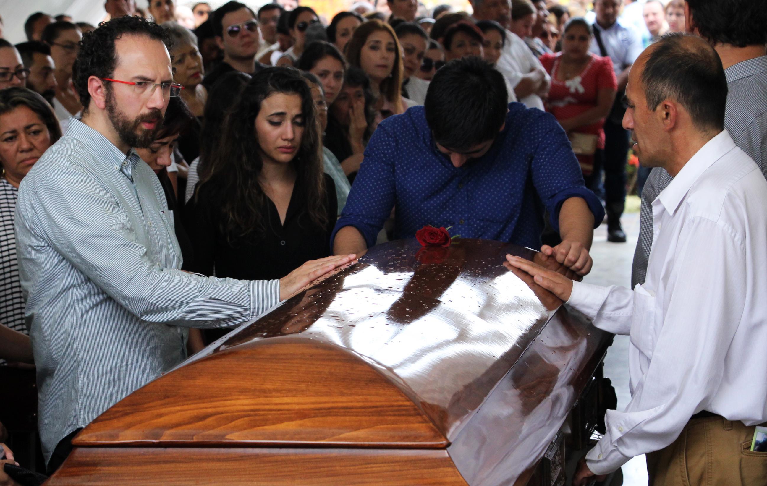 Les proches endeuillés du journaliste assassiné Juan Carlos Huerta se penchent sur son cercueil durant ses funérailles au cimetière de Villahermosa, dans l'État deTabasco le 16 mai 2018.