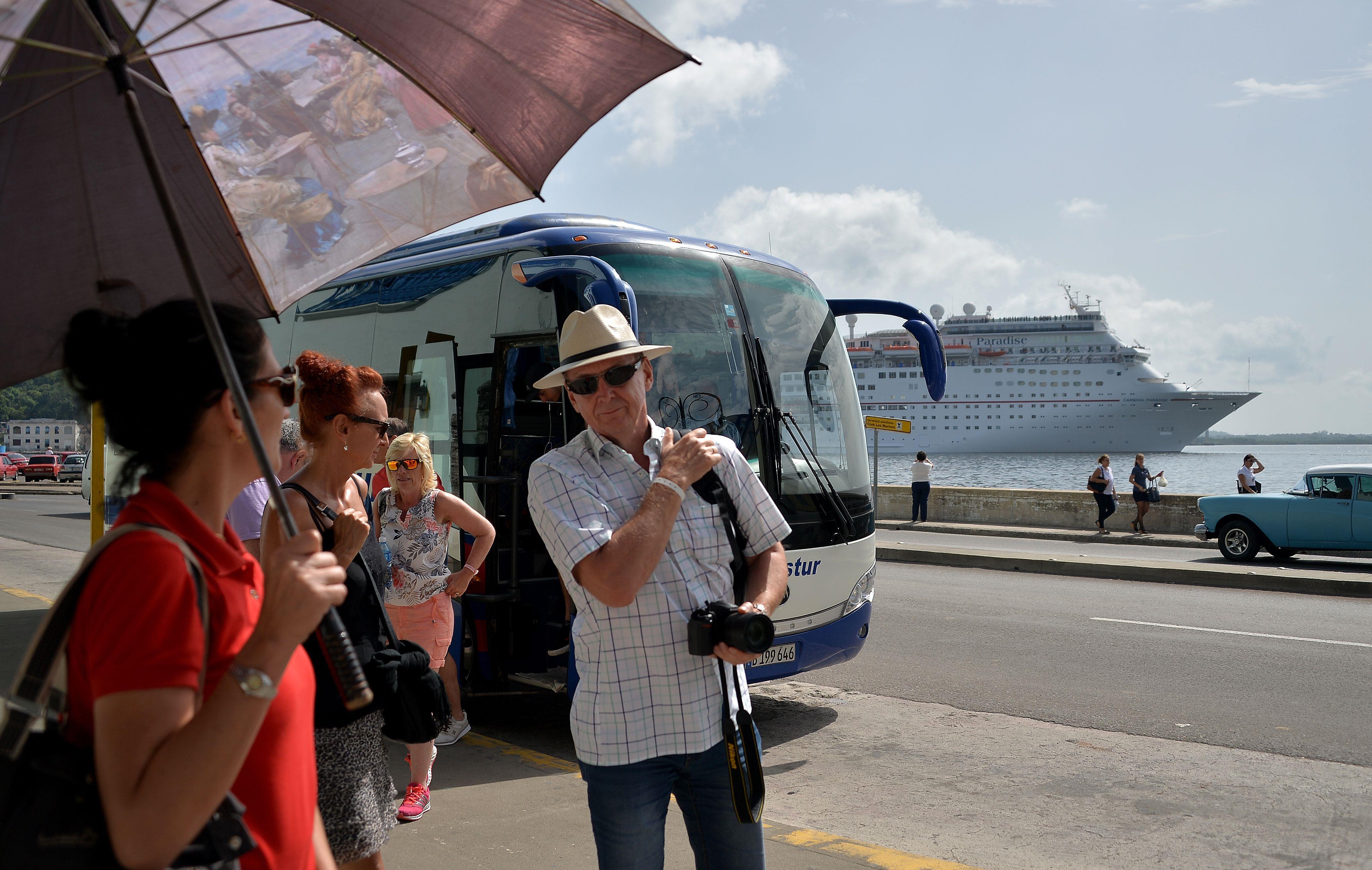Des touristes descendent d'un autocar nolisé devant un bateau de croisière à La Havane, le 10 août 2018.