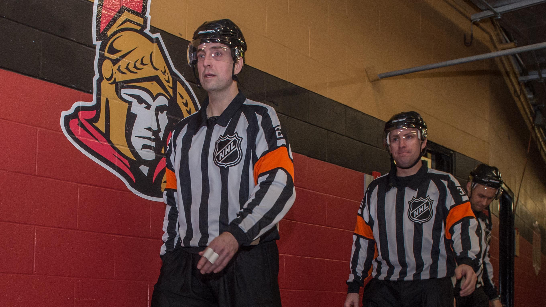 Eric Furlatt (gauche) et ses collègues marchent du vestiaire des arbitres vers la patinoire du Centre Canadian Tire d'Ottawa avant un match entre les Sénateurs et les Flames de Calgary.