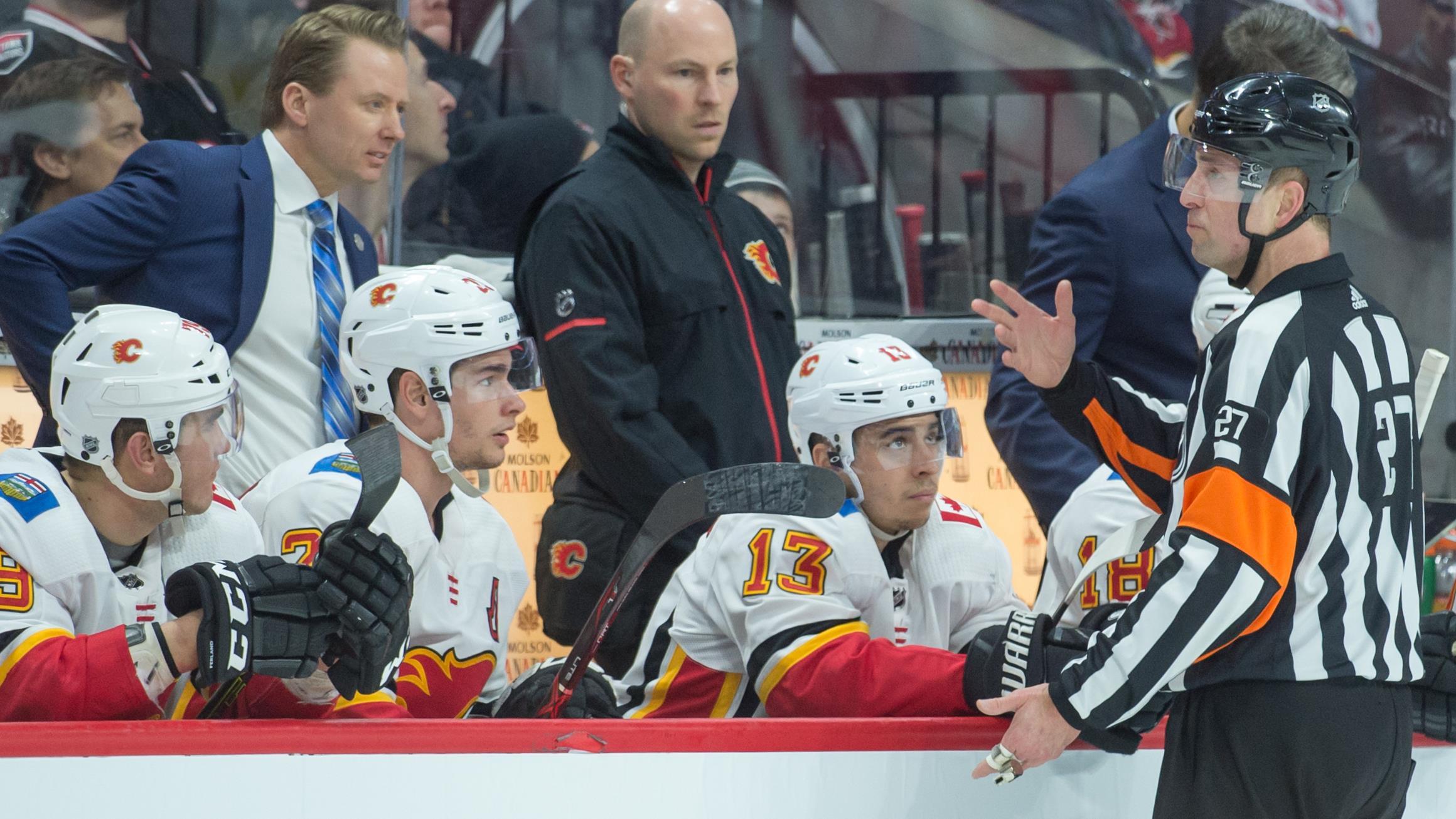 Eric Furlatt discute avec les entraîneurs des Flames de Calgary.