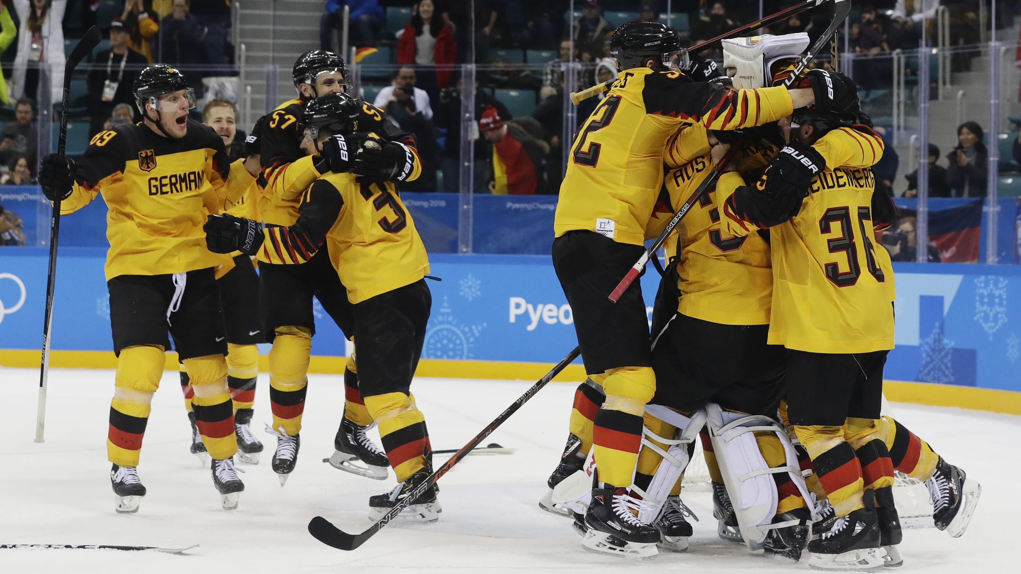 Les joueurs de l'équipe allemande se sautent dans les bras après avoir vaincu le Canada.