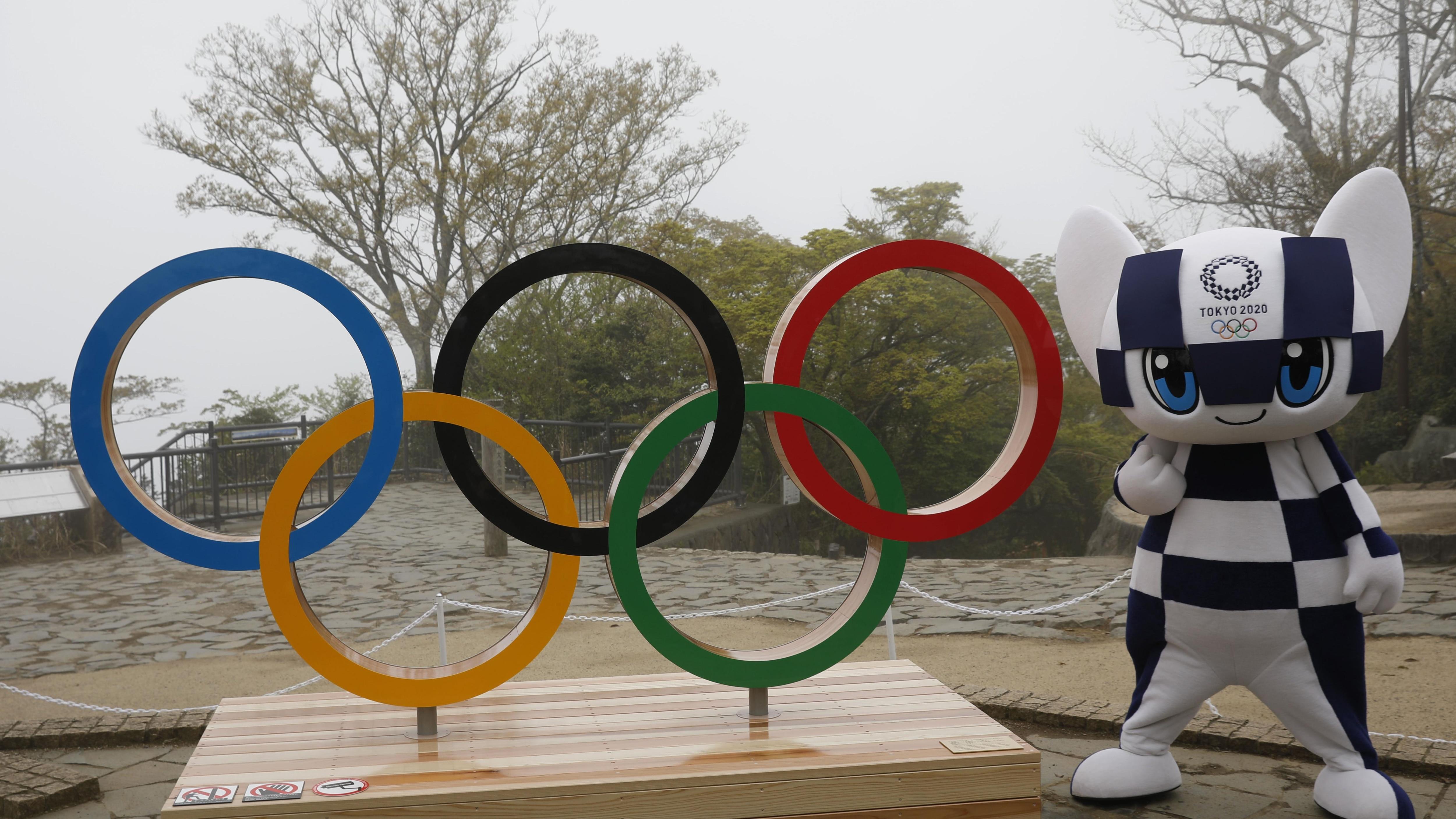 La mascota de los Juegos Olímpicos de Tokio posa junto a los anillos olímpicos.