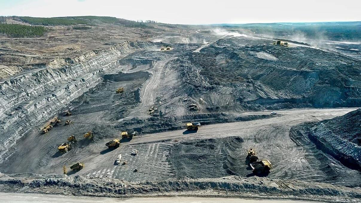 Foto aérea de una mina de carbón en la que se ven varias volquetes y retroexcavadoras.
