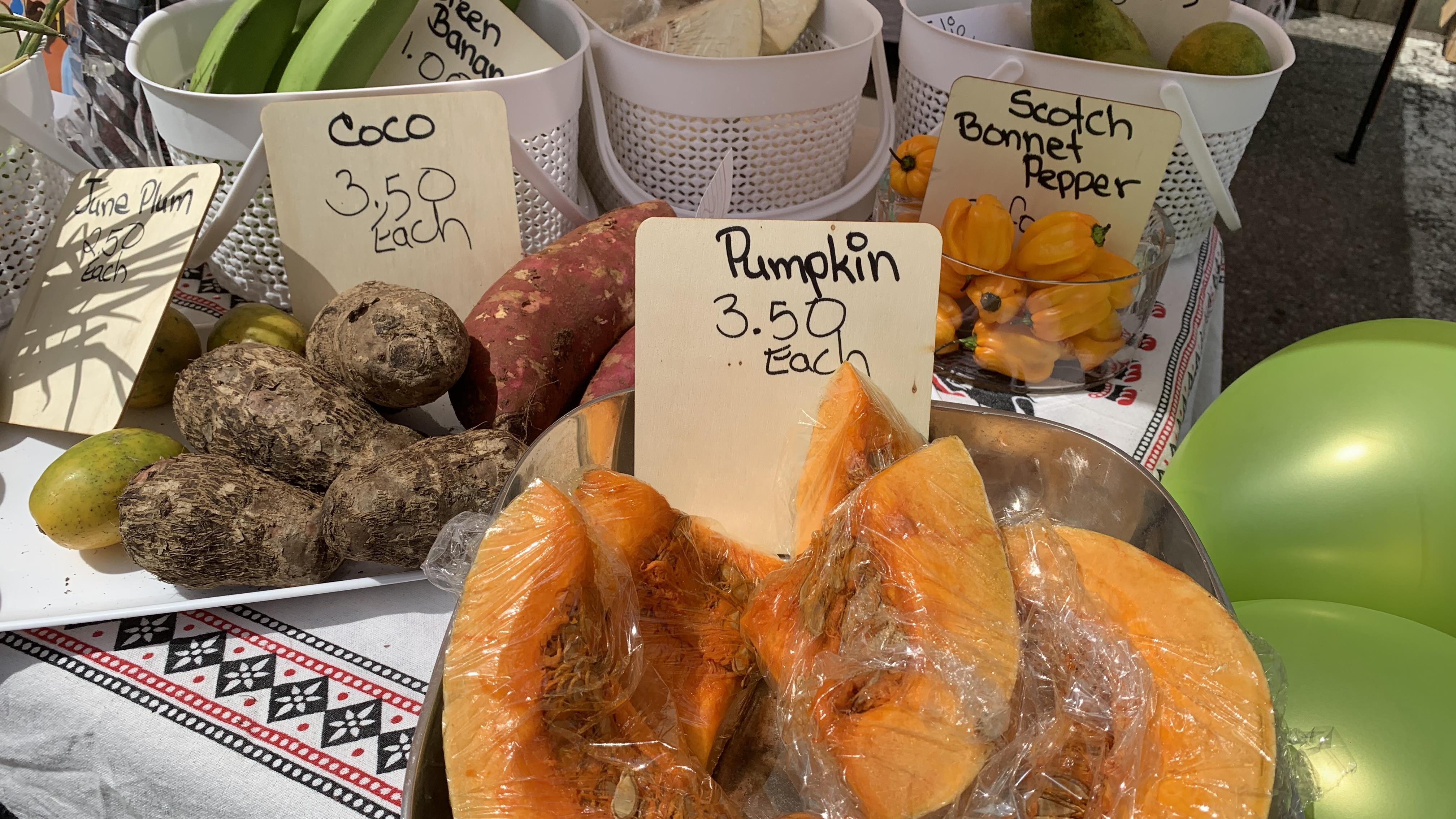 Un étalage de fruits et légumes variés dont de la citrouille, du piment, des mangues.
