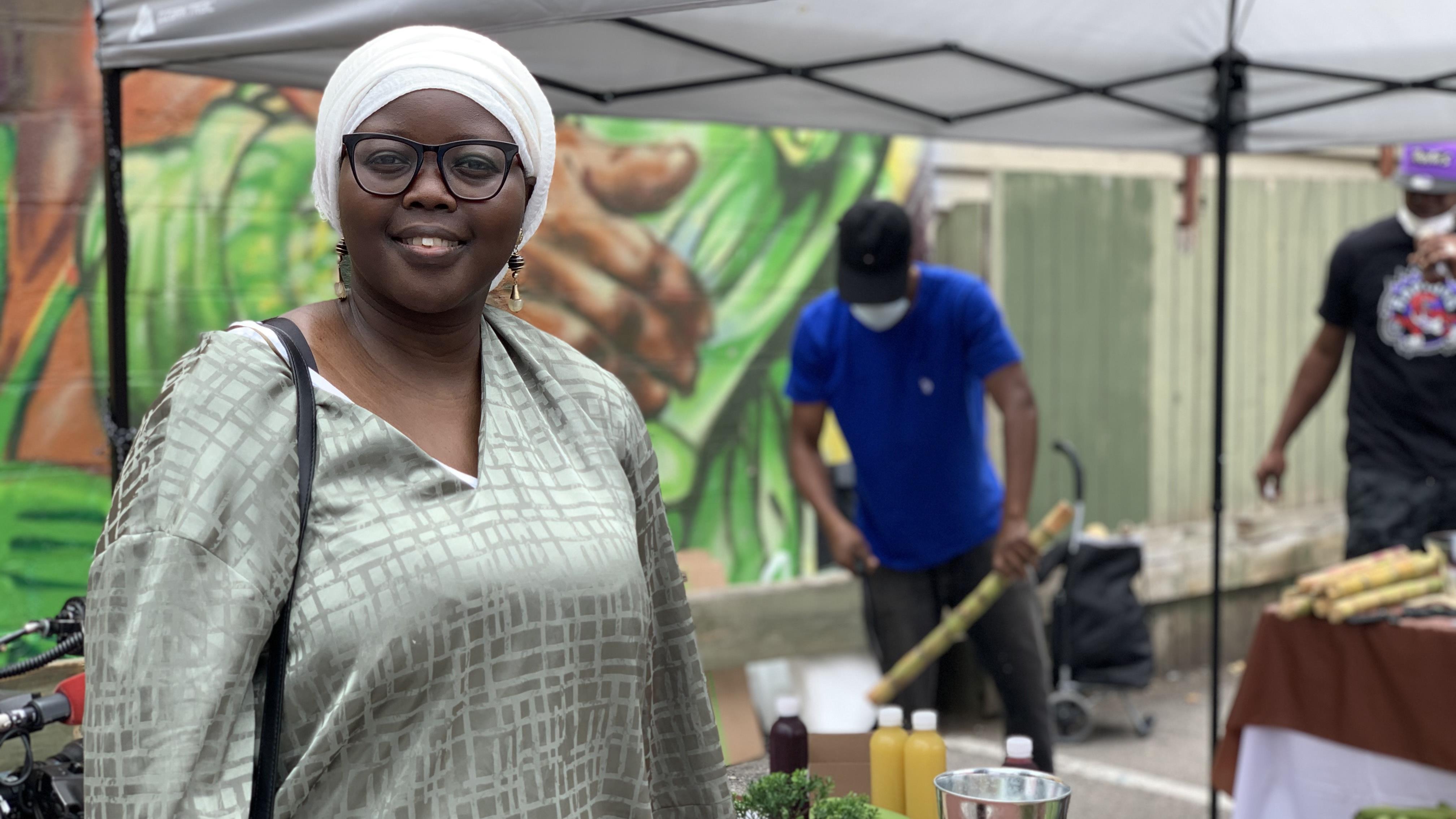 Khadyja Ndoye pose devant une murale pendant qu'une personne coupe de la canne à sucre.