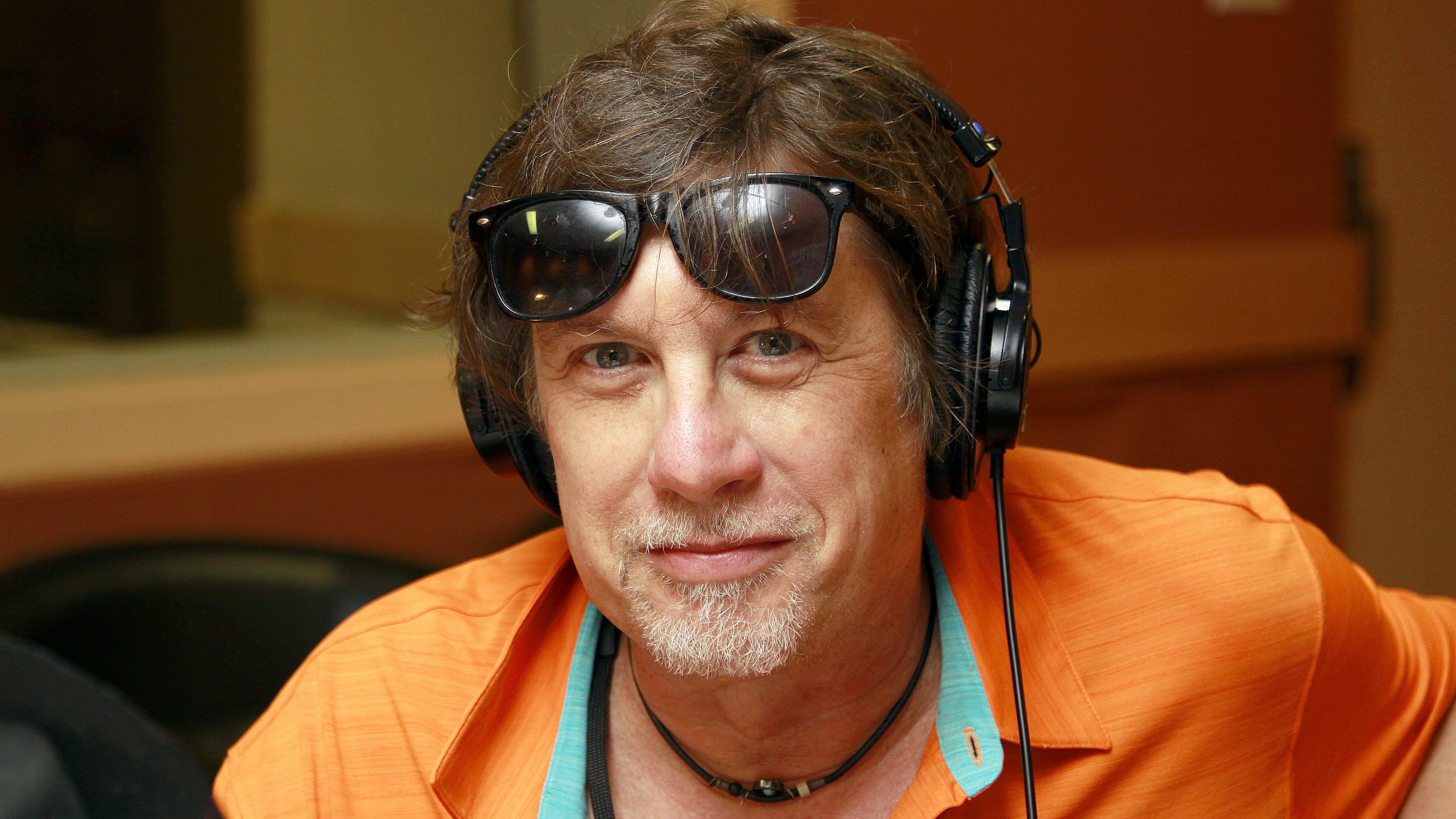 Benoît Rousseau, portant une chemise orange éclatante, sourit dans le studio 18 de Radio-Canada