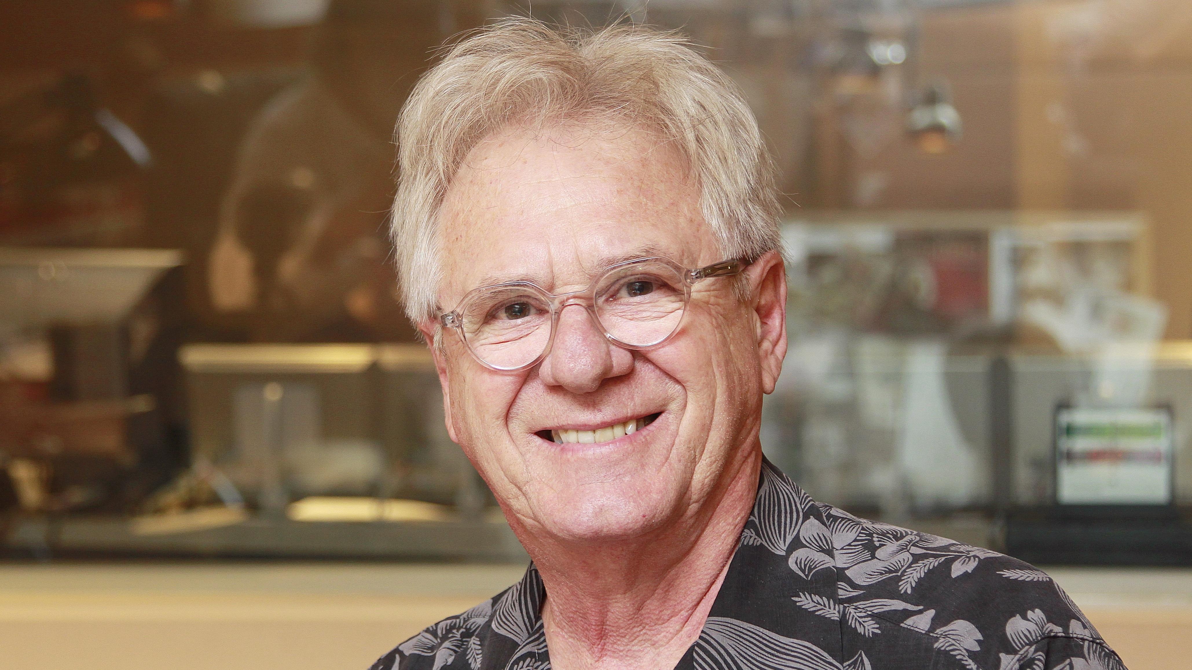 Claude Saucier, souriant, au micro dans le studio 18 de Radio-Canada