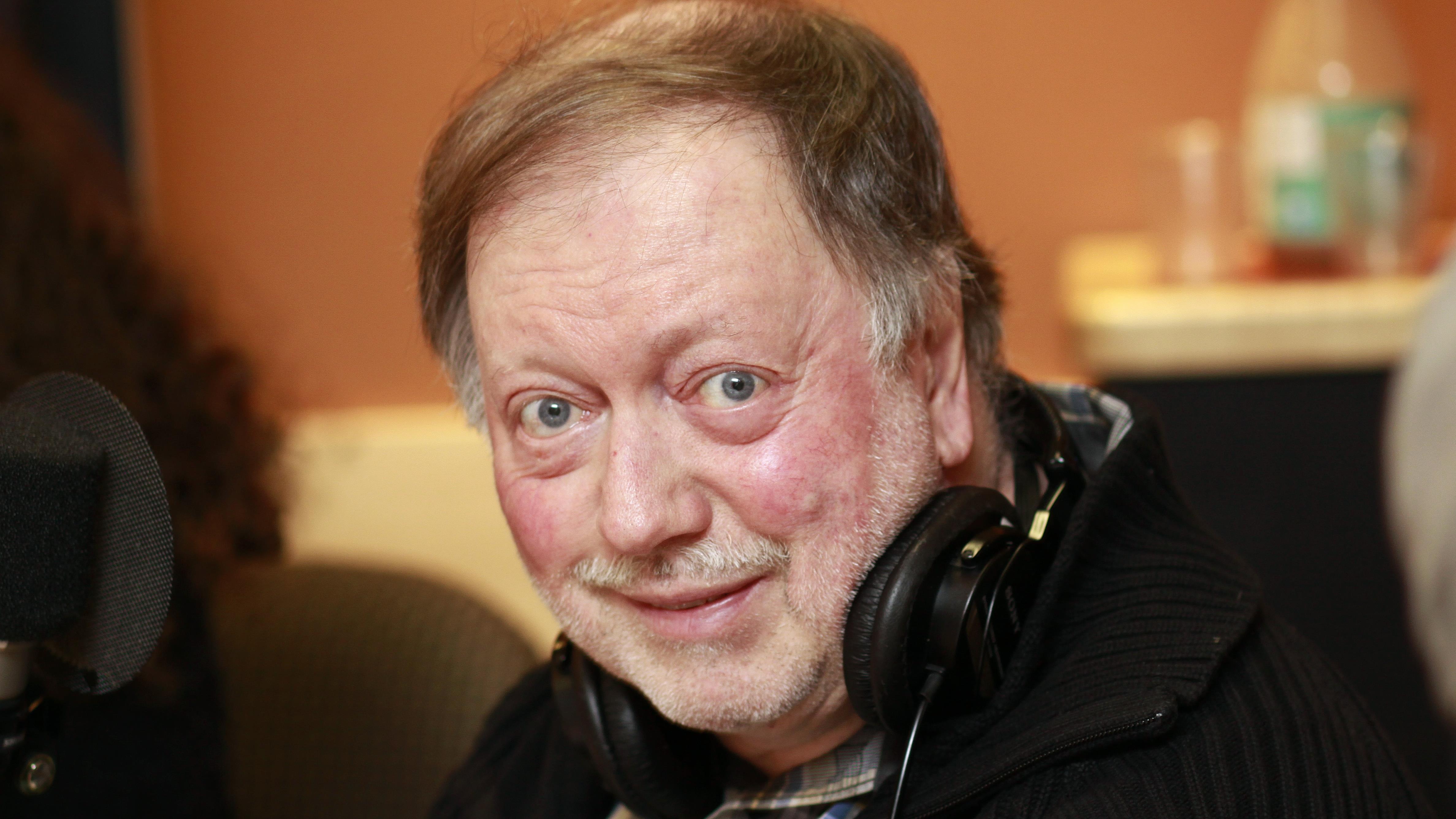 Lionle Levac, vêtu de noir, souriant au micro du studio 18 de Radio-Canada