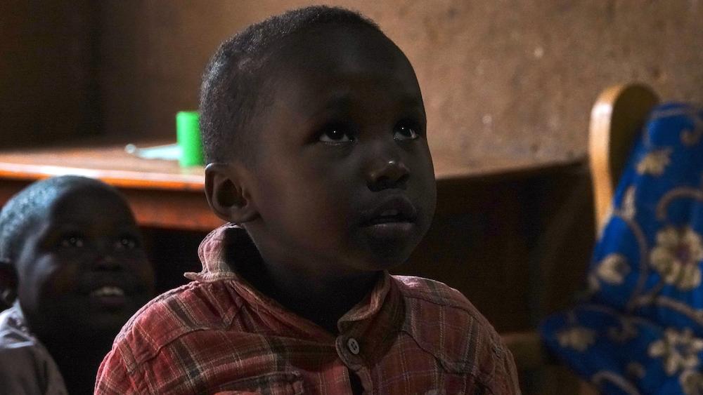 Un enfant rwandais impressionné par la lumière électrique à l'intérieur de sa maison.