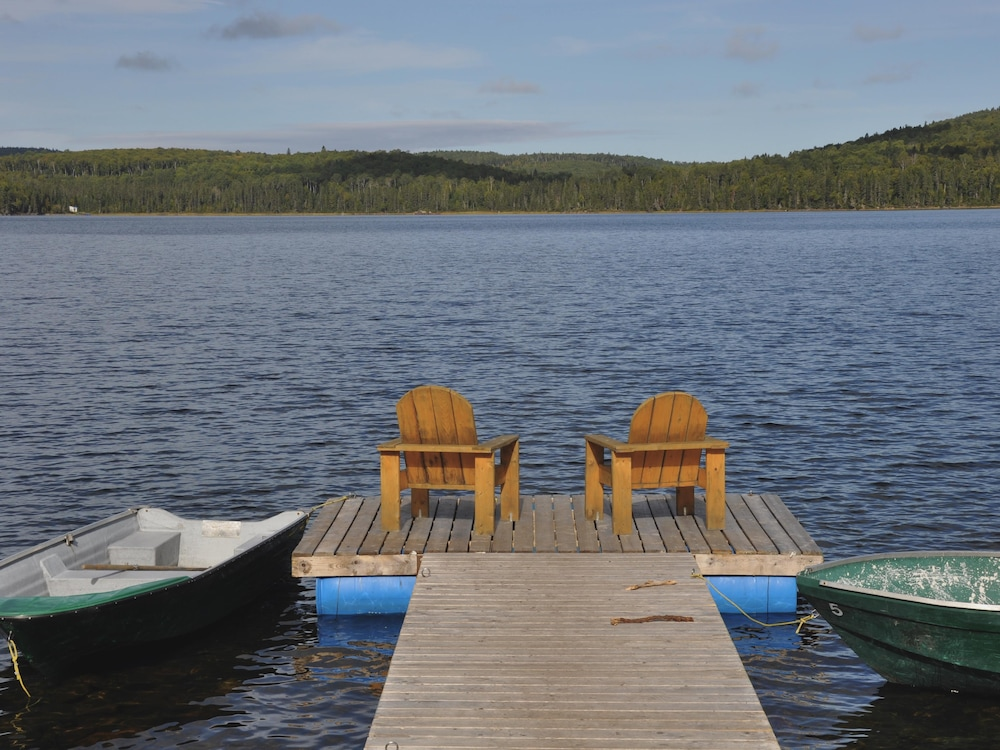 Deux fauteuils Adirondack se trouvent sur le quai d'un lac en Haute-Mauricie. Deux chaloupes flottent de chaque côté.