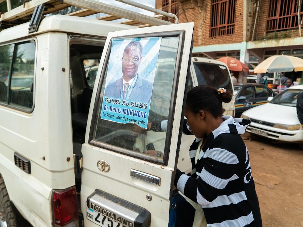 Un véhicule avec une affiche du docteur Mukwege où l'on peut lire qu'il est le « porte-voix des sans voix ».