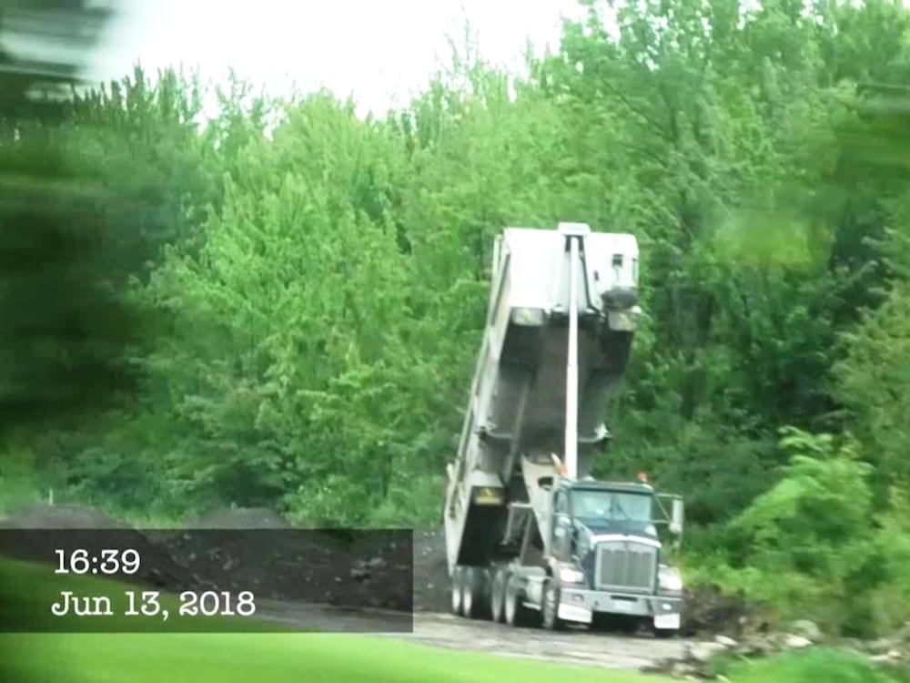 Un camion déverse des sols dans la nature.