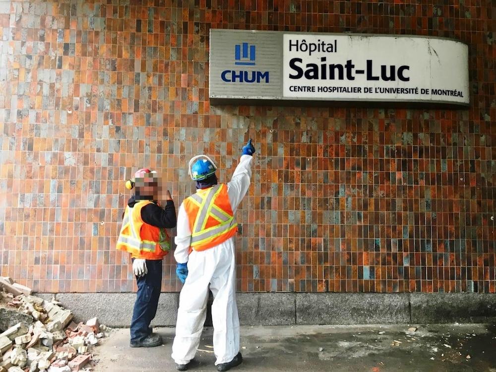 Des hommes, portant des casques de construction, regardent une affiche de l'hôpital Saint-Luc.