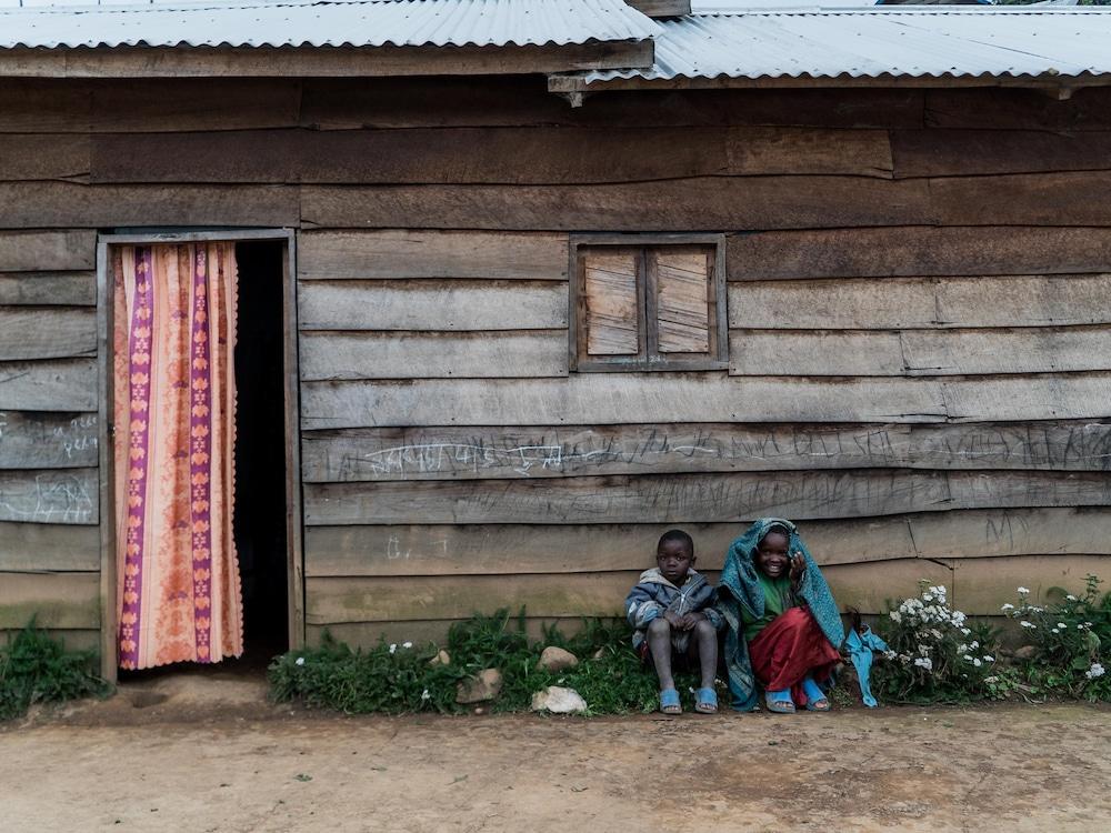 Deux enfants devant leur maison.