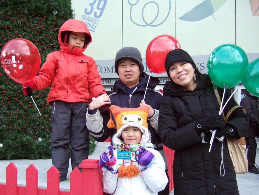 La famille de Léna, souriante, avec des ballons de fête