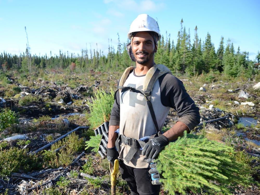 Jamalsky Saint-Fleur prend la pose avec son équipement de planteur d'arbres. Il porte un casque et une ceinture à laquelle des petits plants sont accrochés. Il tient une pelle dans sa main gauche.