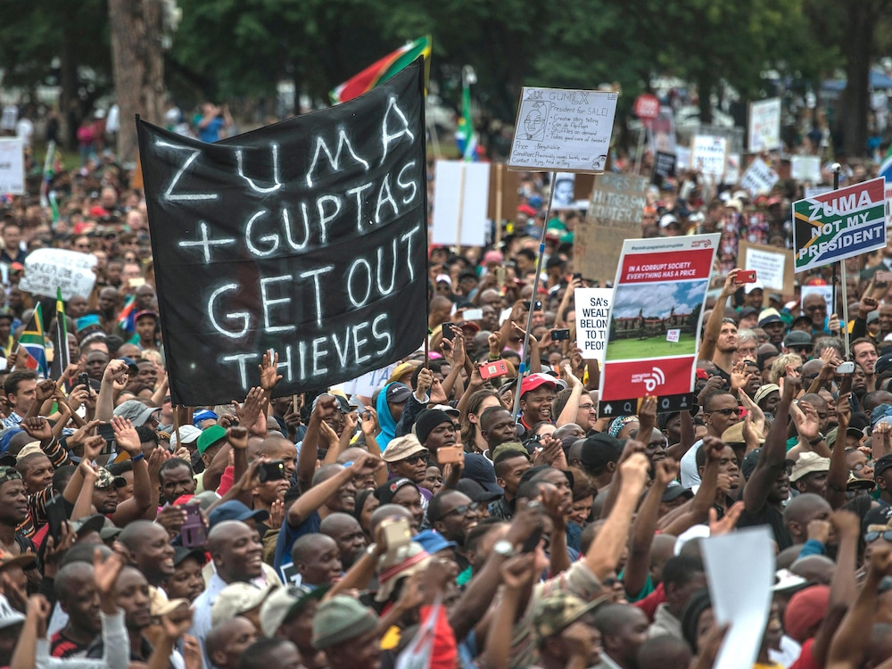 Une foule manifeste avec des affiches dénonçant le gouvernement.