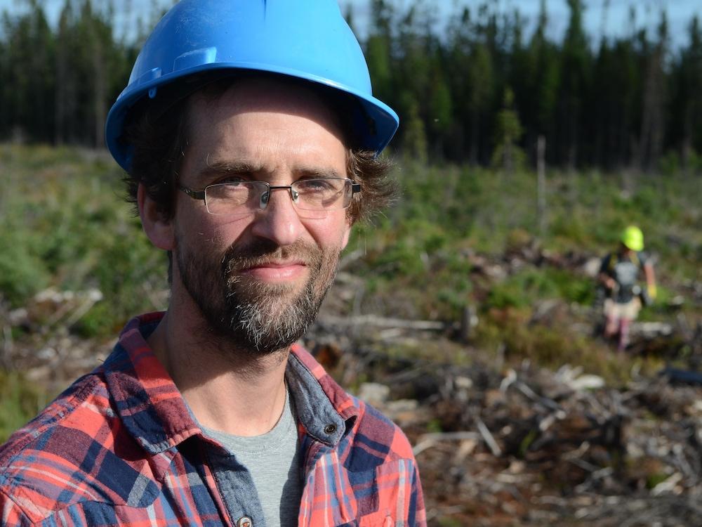 Denis Beaulieu porte un casque et une chemise à carreaux. Un planteur d'arbres s'active en arrière-plan.