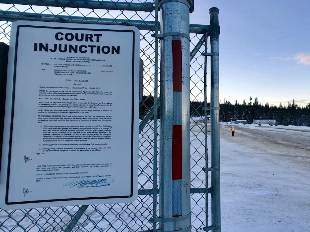 Une affiche sur une clôture indique qu'une injonction empêche les opposants au projet de manifester à proximité du site.