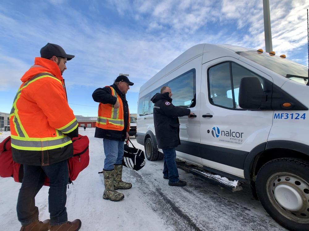 Trois travailleurs s'apprêtent à monter à bord d'une camionnette pour se rendre au chantier de Muskrat Falls.