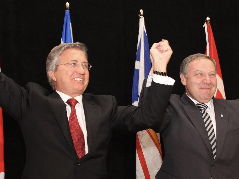 Deux hommes lèvent les mains.