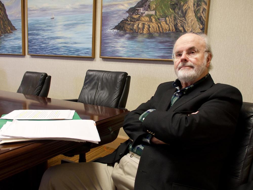 Un homme assis dans une salle de conférence.
