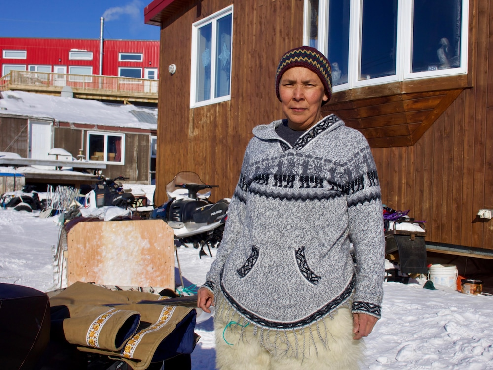 Devant sa maison, Meeka Mike se prépare à la chasse au phoque.