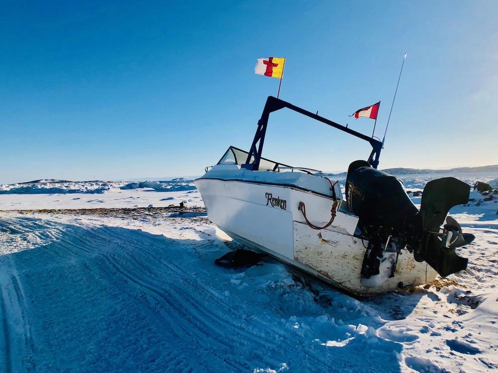 Les drapeaux du Nunavut et du Canada flottent sur un bateau qui attend l'arrivée de l'été dans la baie de Frobisher.