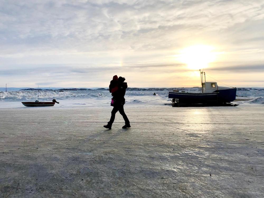 Une mère marche avec son enfant dans les bras à proximité de la baie de Frobisher, à Iqaluit.