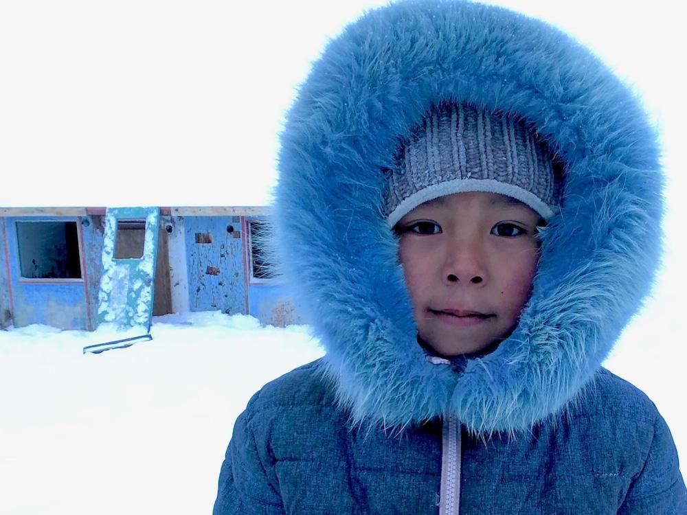 Une jeune Inuite devant une maison abandonnée dans la communauté insulaire de Qikiqtarjuaq. Le logement représente un énorme défi de santé publique au Nunavut.