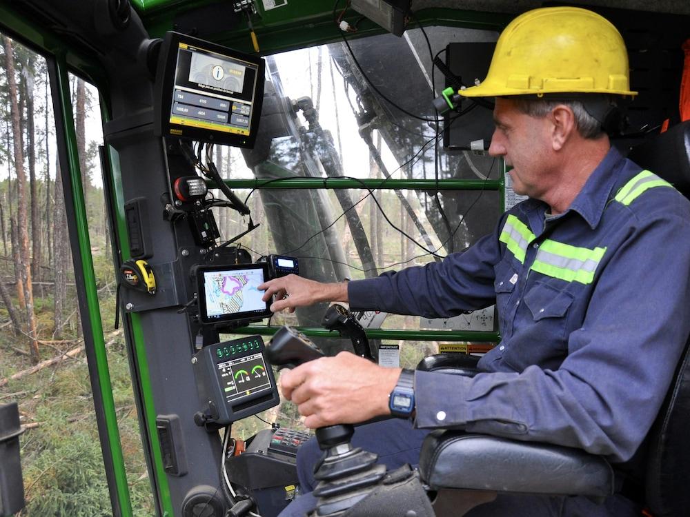 Intérieur de la cabine d'une abatteuse multifonctionnelle dans laquelle l'opérateur pointe le système GPS.