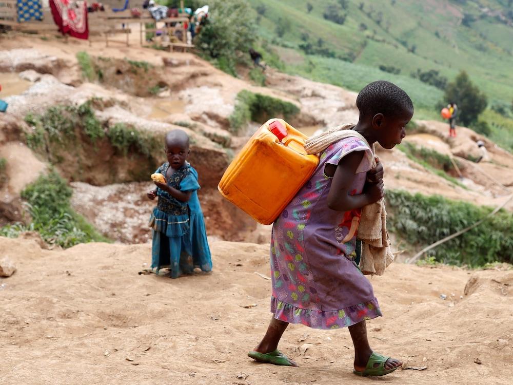 Une fillette d'une dizaine d'années marche en portant un bidon sur son dos.