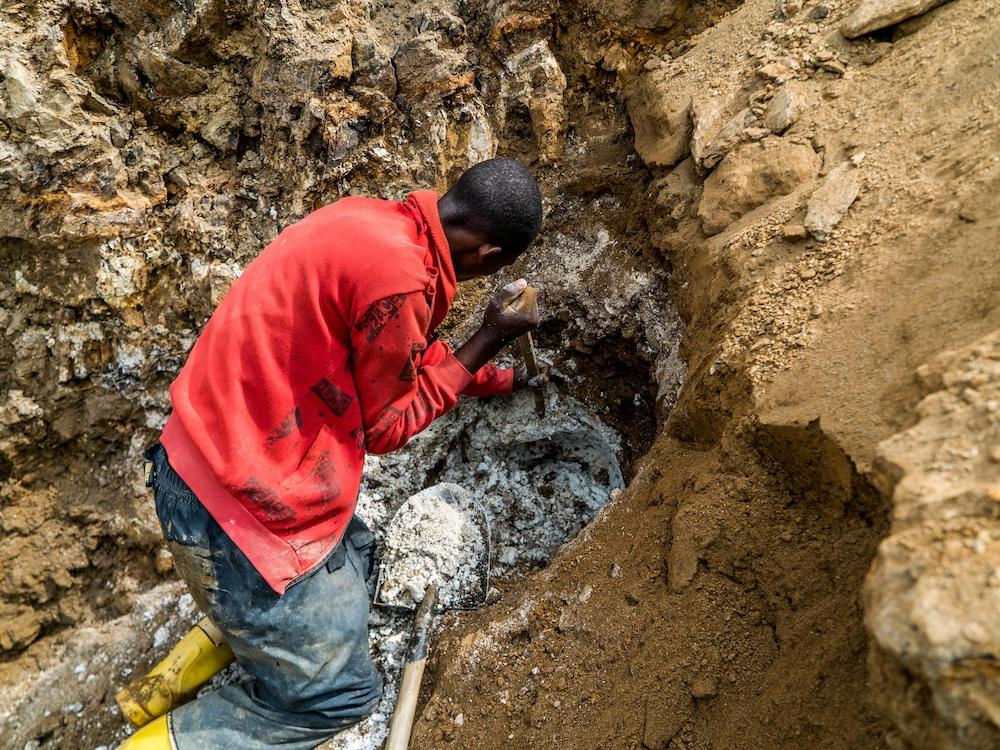 Un homme creuse la roche avec un pic.
