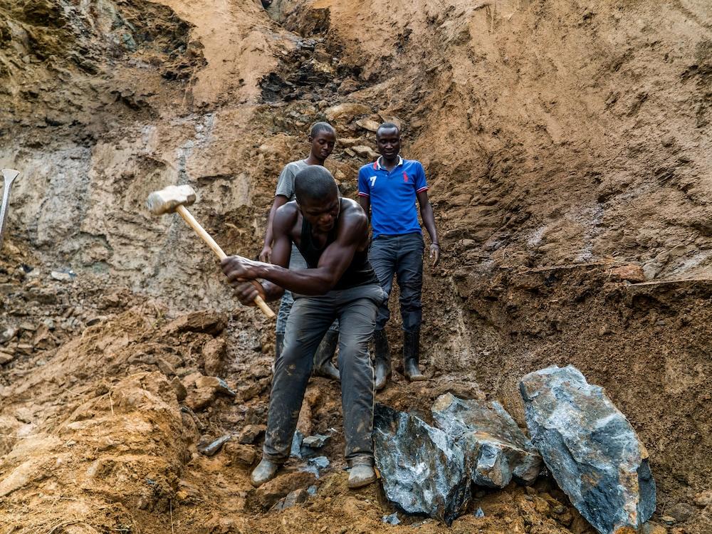 Des hommes creusent la paroi rocheuse.