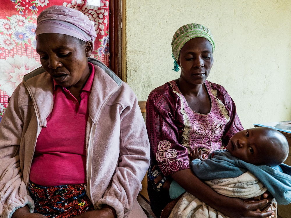 Deux femmes assises regardent le sol, celle de droite porte un jeune enfant dans ses bras.