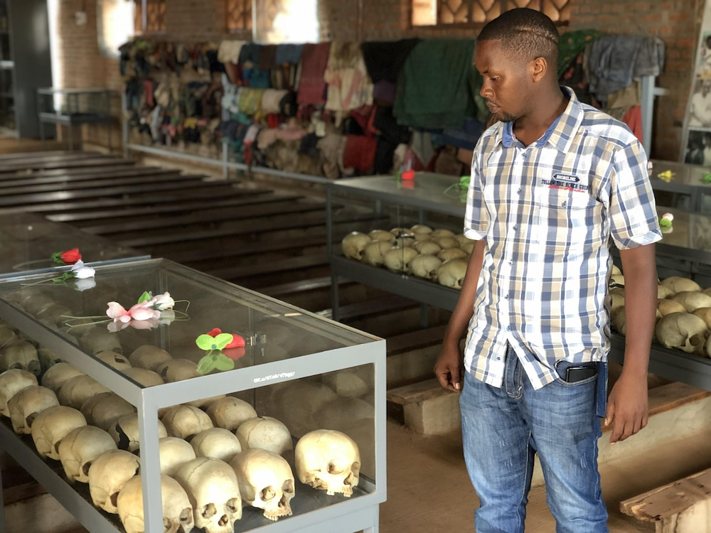 Edmond Niyonsaba regarde des crânes exposés dans une vitrine.