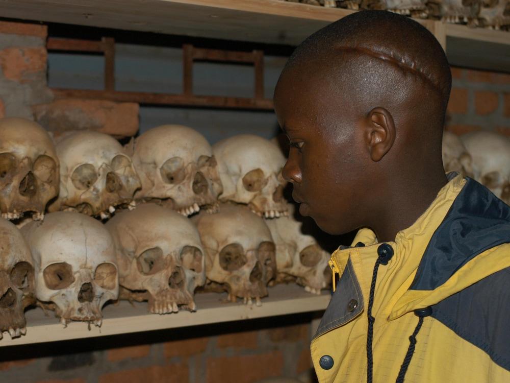 Le jeune Edmond Niyonsaba regarde des crânes empilés sur des étagères. Une longue cicatrice est clairement visible sur sa tête.