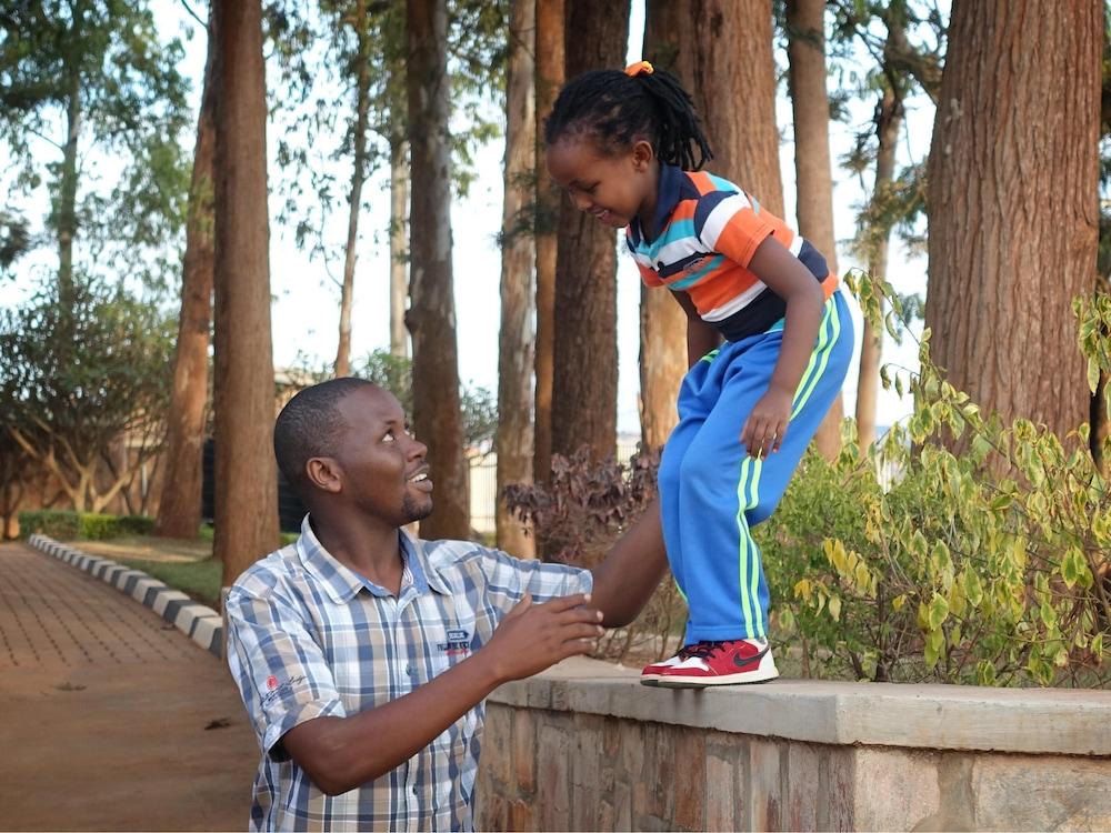 M. Niyonsaba joue avec sa fillette dans un parc.