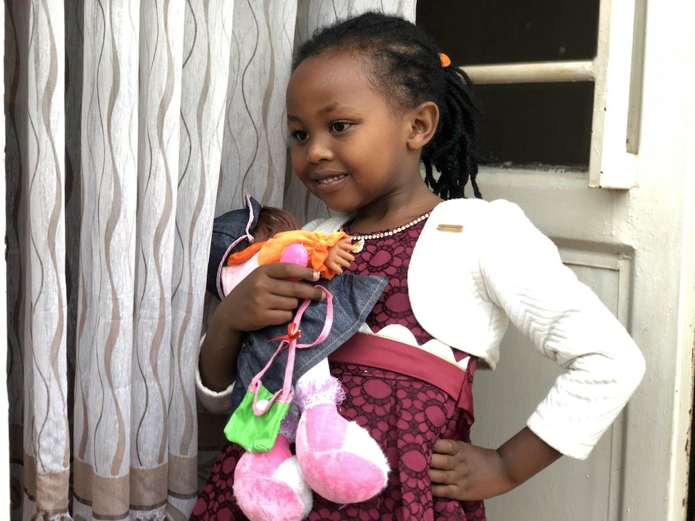 La petite fille, vêtue d'une robe élégante, tient une poupée dans ses bras.