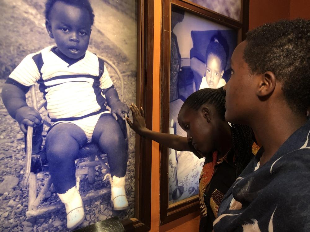 Des jeunes regardent la photo en noir et blanc d'un bambin.