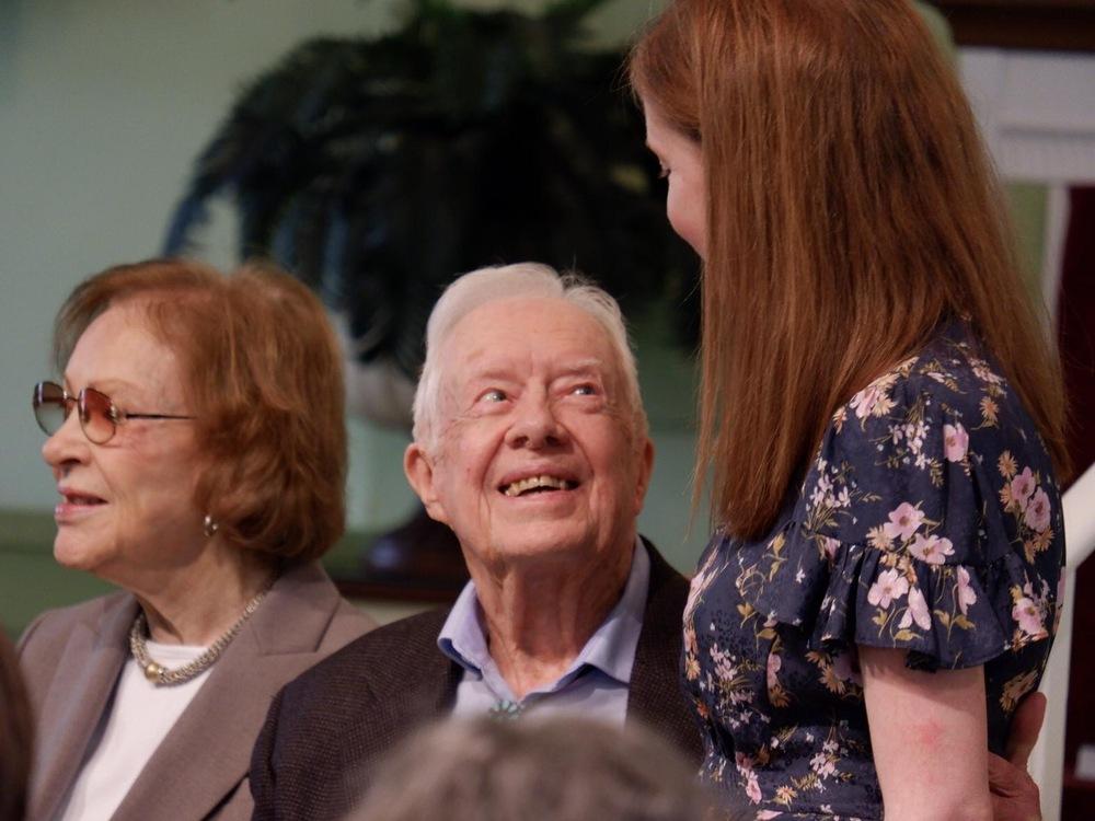 Jimmy Carter discute avec une jeune femme.