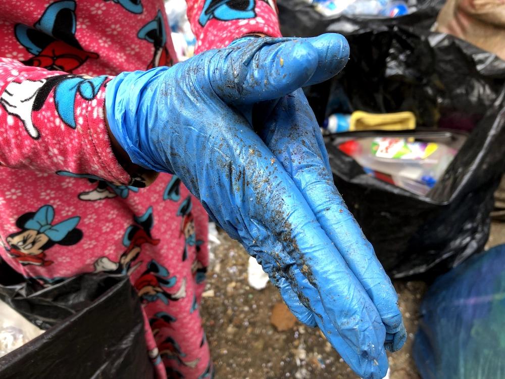 Une femme montre les gants avec lesquels elle trie les déchets.