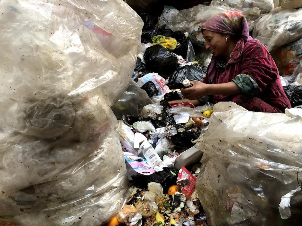 Une femme trie les déchets sans gants.