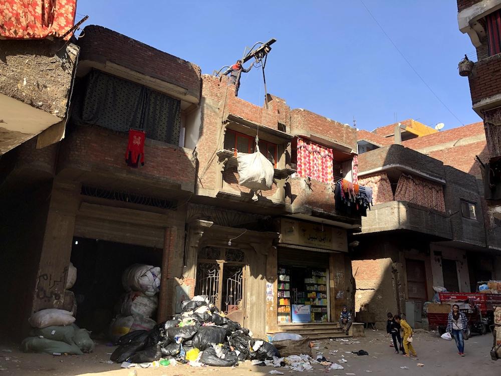 Un homme utilise un palan à corde pour stocker des matériaux recyclables sur le toit de son immeuble.
