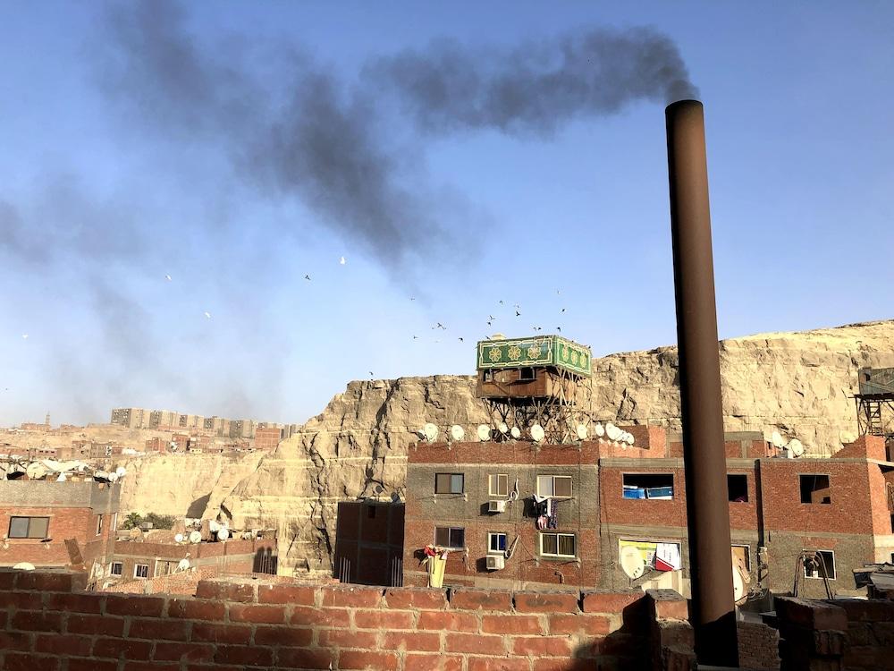 Une fumée noire sort d'une cheminée sur le toit d'un immeuble de Manshiyat Nasser.