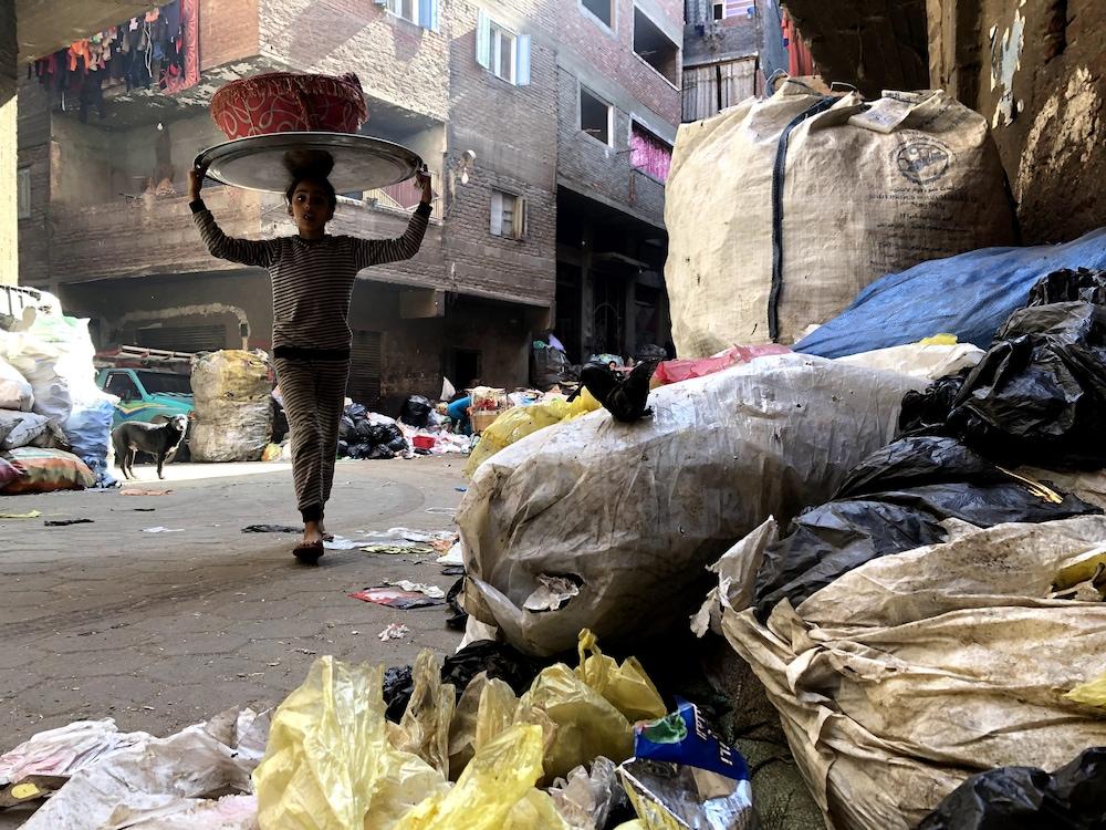 Une enfant traverse une rue avec un plateau sur la tête.