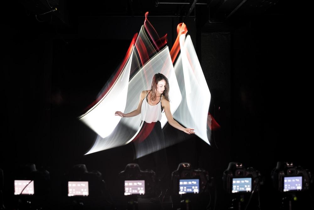 Prise de vue de Kim Henry sous un voile de lumière, devant plusieurs caméras automatisées.