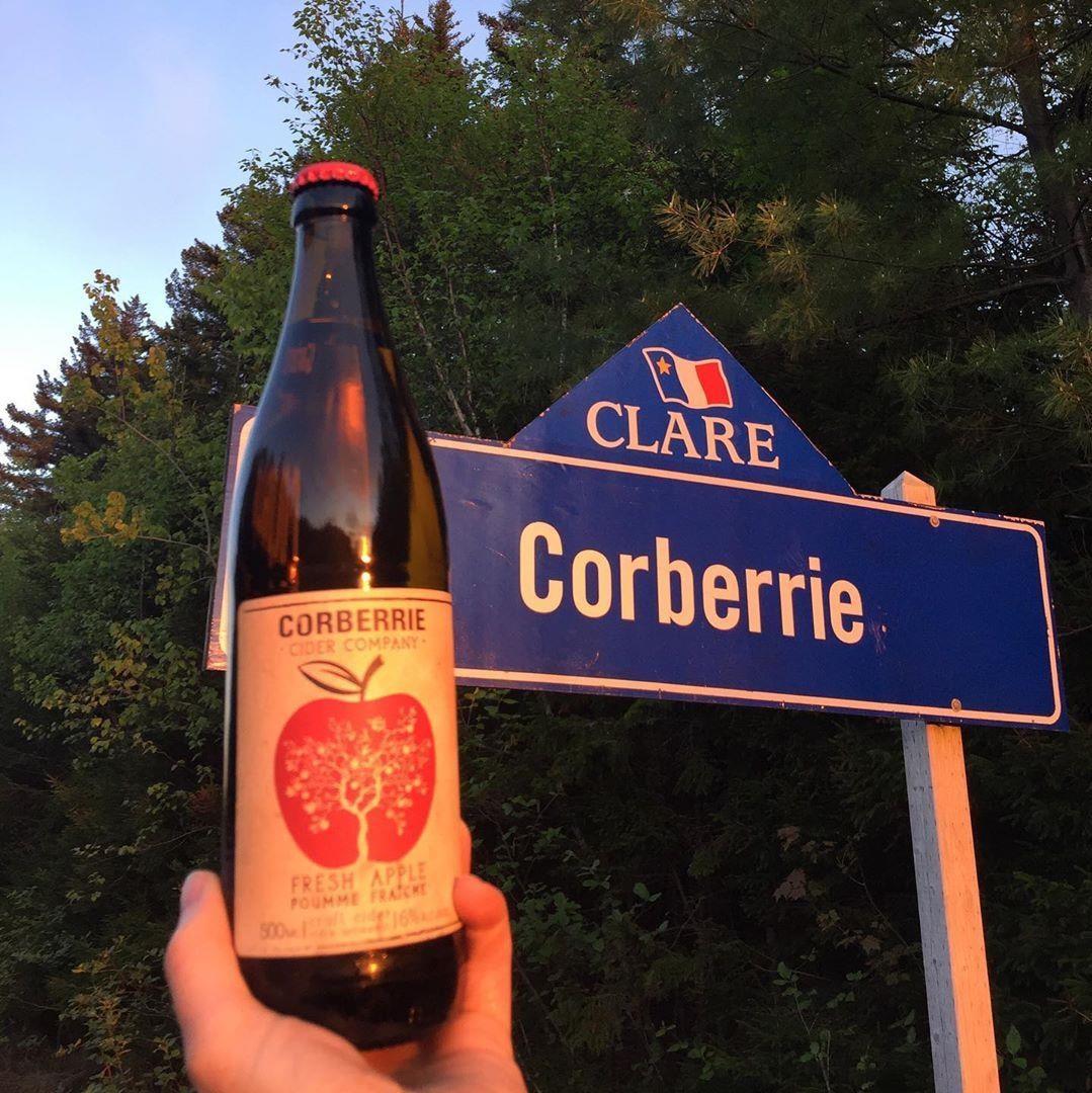Bouteille de cidre Corberrie devant un panneau routier annonçant la communauté de Corberrie et la Municipalité de Clare.