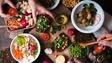 Des personnes se servent à manger à partir d'une table emplie de diverses plats de cuisine végane.