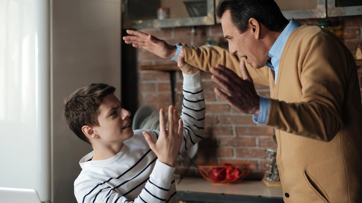 Une discussion animée entre un père et son adolescent.